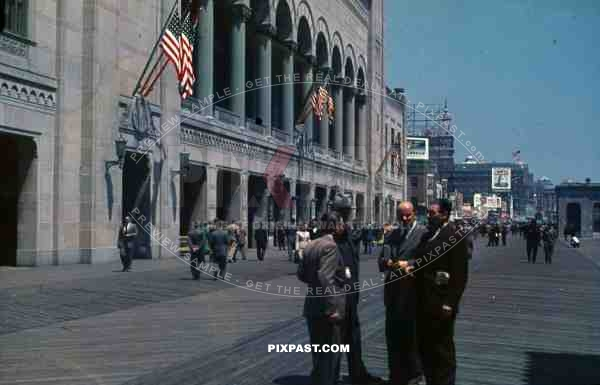 PostW color 1947 New York board walk shops bank american flag german tourists