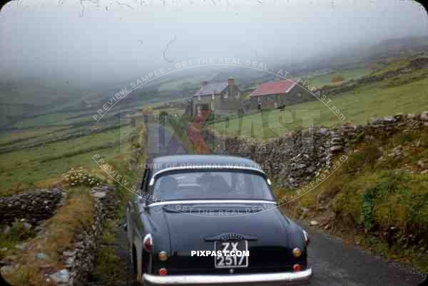 Wicklow Gap Ireland 1953, old timer vintage car in country roads, stone walls and house